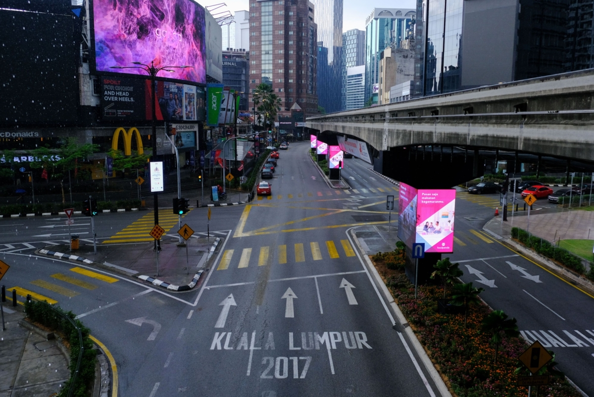Closed stores line an empty road at Jalan Bandar near Petaling street in Kuala Lumpur, Malaysia, on Wednesday, March 18, 2020. Prime Minister Muhyiddin Yassin said late Monday that the country will be limiting non-essential businesses operations as well as banning all visitors from entering the country and residents from traveling overseas from March 18 for two weeks. (Photographer: Samsul Said/Bloomberg)