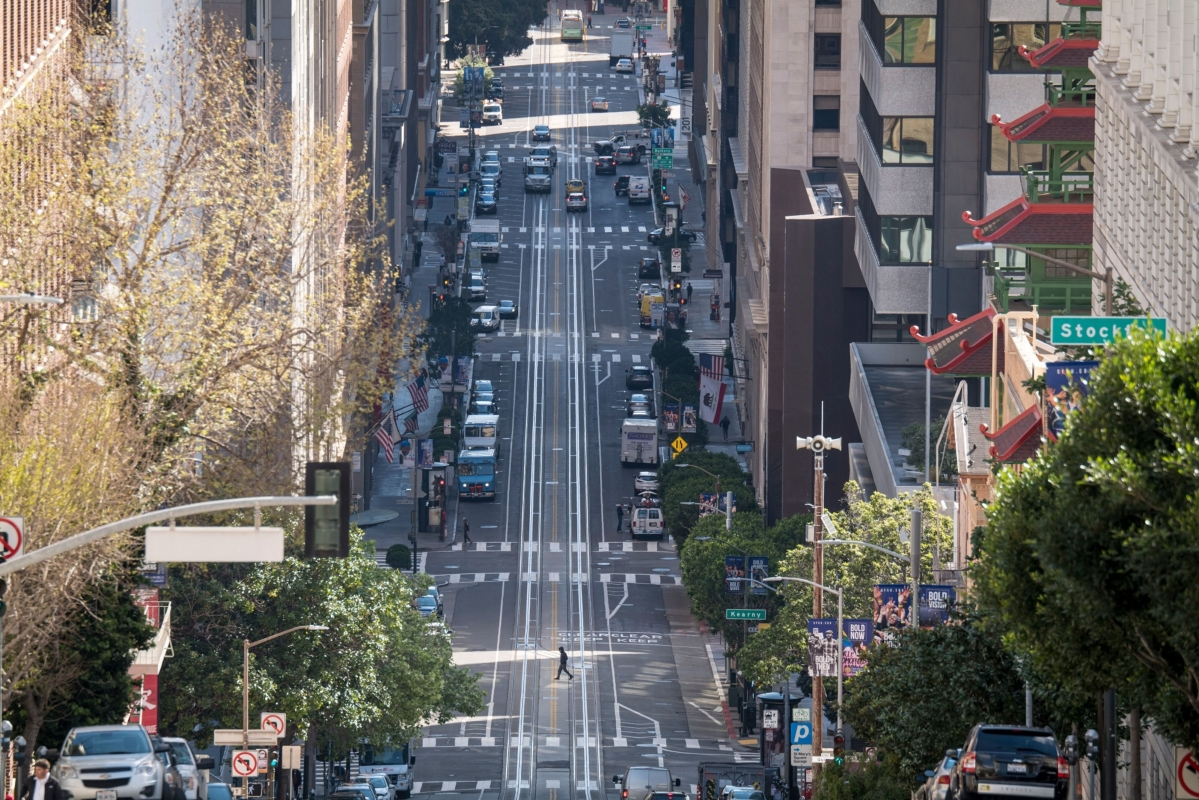 A pedestrian crosses an empty California Street during rush hour in San Francisco, California, U.S., on Tuesday, March 17, 2020. Six of the biggest counties in the San Francisco Bay Area ordered people to stay home except for essential needs, marking one of the nation's strongest local efforts yet to stem the spread of the coronavirus. (Photographer: David Paul Morris/Bloomberg)