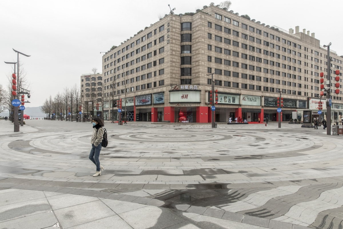 A pedestrian wearing a face mask walks through an empty shopping plaza, in view of a Hennes & Mauritz AB (H&M) store, in Hangzhou, China, on Tuesday, Feb. 11, 2020.  (Photographer: Qilai Shen/Bloomberg)