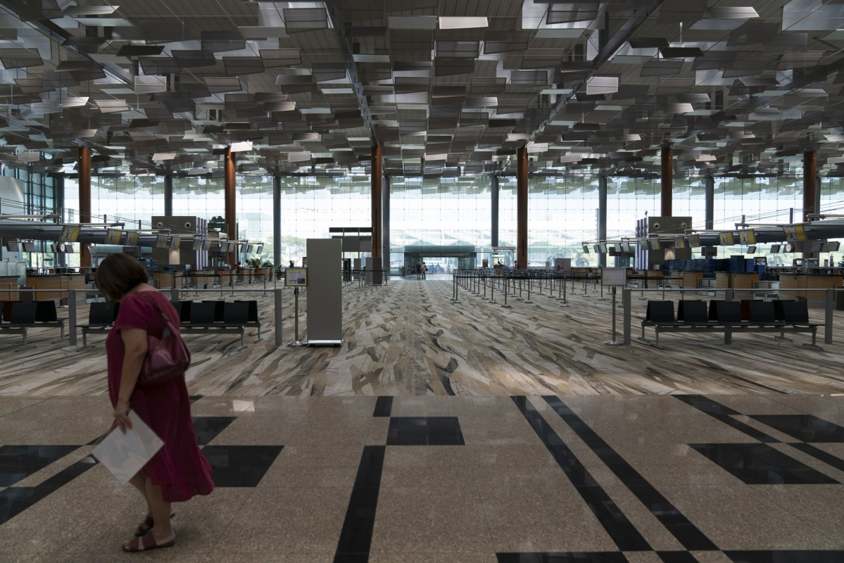 A woman walks past an empty check-in area in Terminal 3 at Singapore Changi Airport in Singapore, on Tuesday, March 17, 2020. All arrivals to Singapore from the Asean group of nations as well as Japan, Switzerland and U.K. will have to self-isolate for two weeks in the city-state's latest measure to tackle the coronavirus pandemic. (Photographer: Wei Leng Tay/Bloomberg)