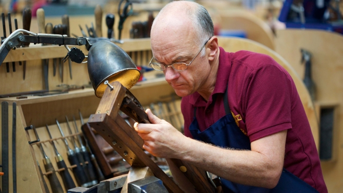 A master craftsman checks out the chequering on a gunstock. The better the chequering, the better the grip of a gun.