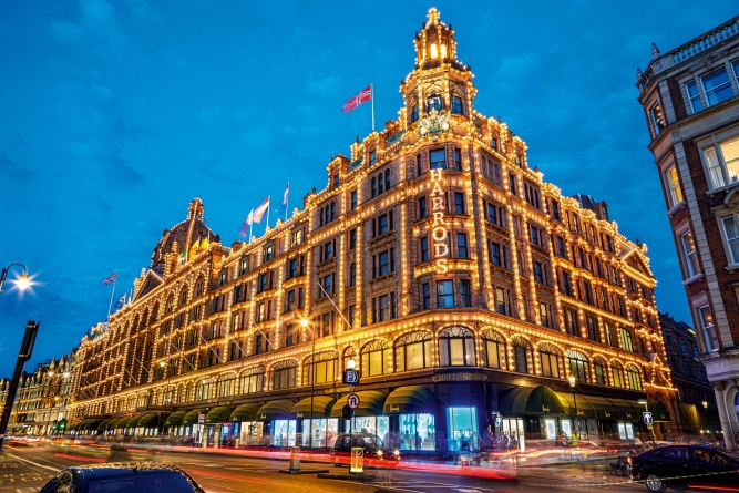 Harrods department store illuminated in the evening in London.