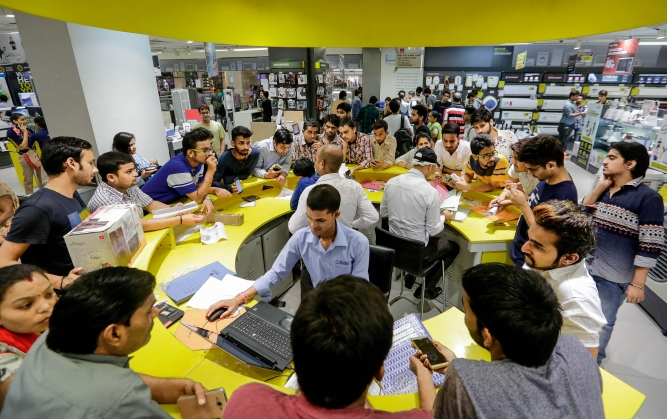 Employees serve customers at a service counter at a Reliance Digital store, a subsidiary of Reliance Industries Ltd., in New Delhi.