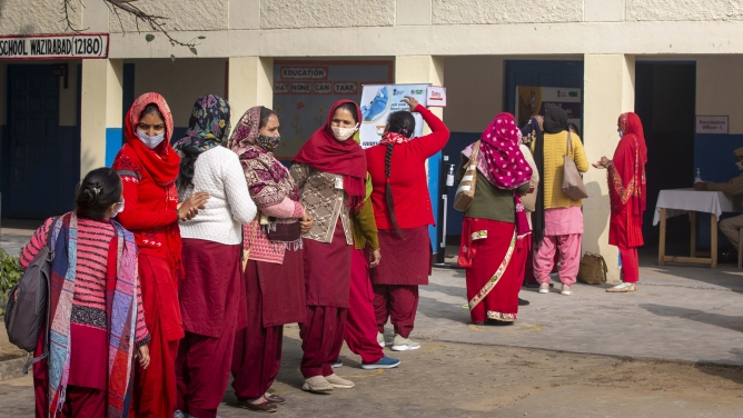 Health workers wait for their turn outside a Covid-19 vaccination centre in Gurugram.