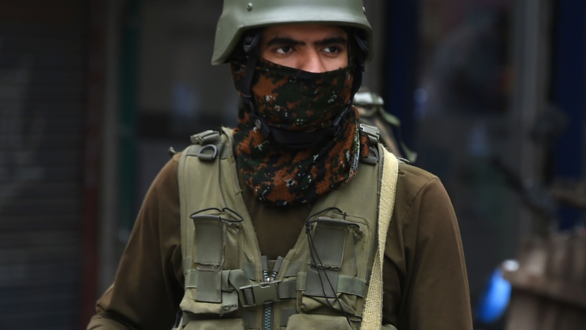 An Indian paramilitary trooper stands guard outside a bunker in south Kashmir's Anantnag district on June 12, 2019