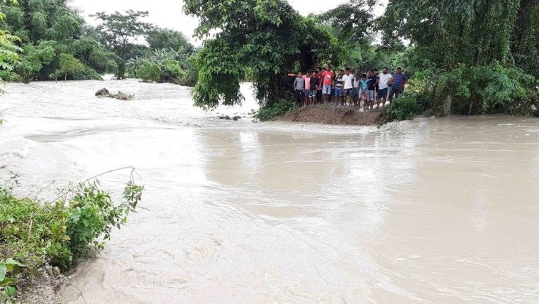 People stand on a damaged embankment washed out by the flood in Assam