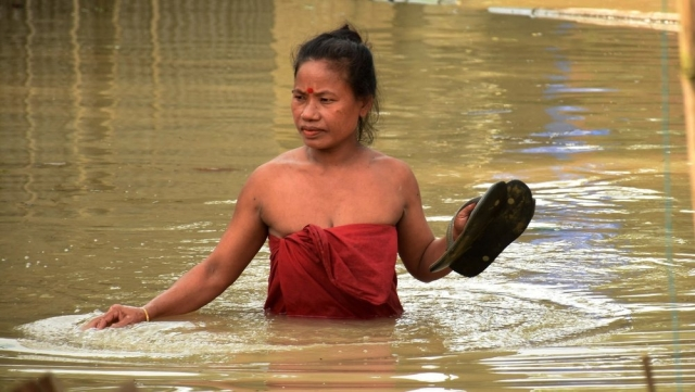 A woman wades through a flooded area following heavy monsoon rain at Panikhaiti in Kamrup