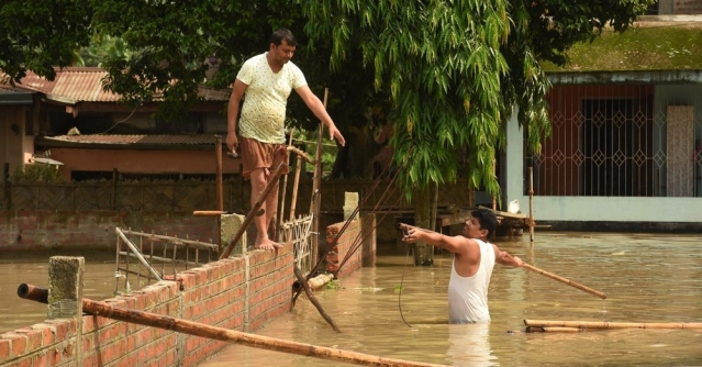 People prepare a route from bamboo to move to a safer place from their submerged house following heavy monsoon rain at Panikhaiti in Kamrup district of Assam