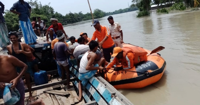 NDRF personnel rescue the residents using boats from the flood-affected area of Morigaon