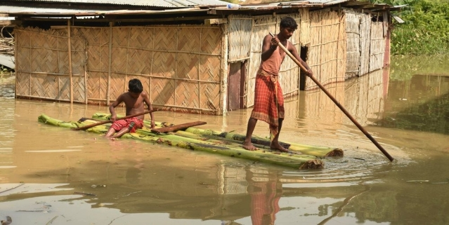 People using Banana raft move to a safer place on a boat from a flood-affected area, at Panikhaiti in Kamrup district of Assam