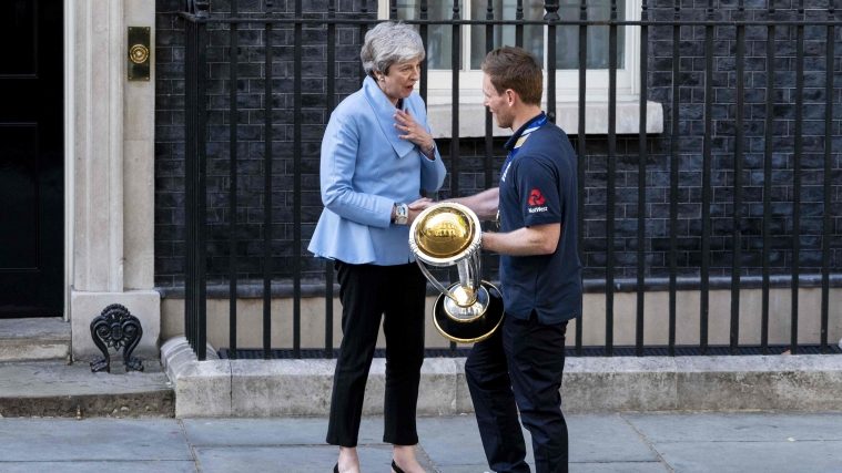 Britain's Prime Minister Theresa May (L) speaks with England's captain Eoin Morgan (R), holding the World Cup trophy, outside 10 Downing Street as England players arrive for a reception in London on July 15, 2019