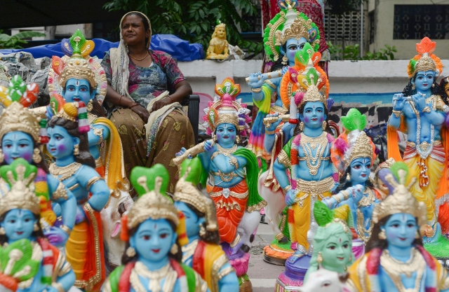 A vendor sits as she sells models of the Hindu deity Krishna on display at a roadside ahead of the 'Janmashtami' festival in Chennai