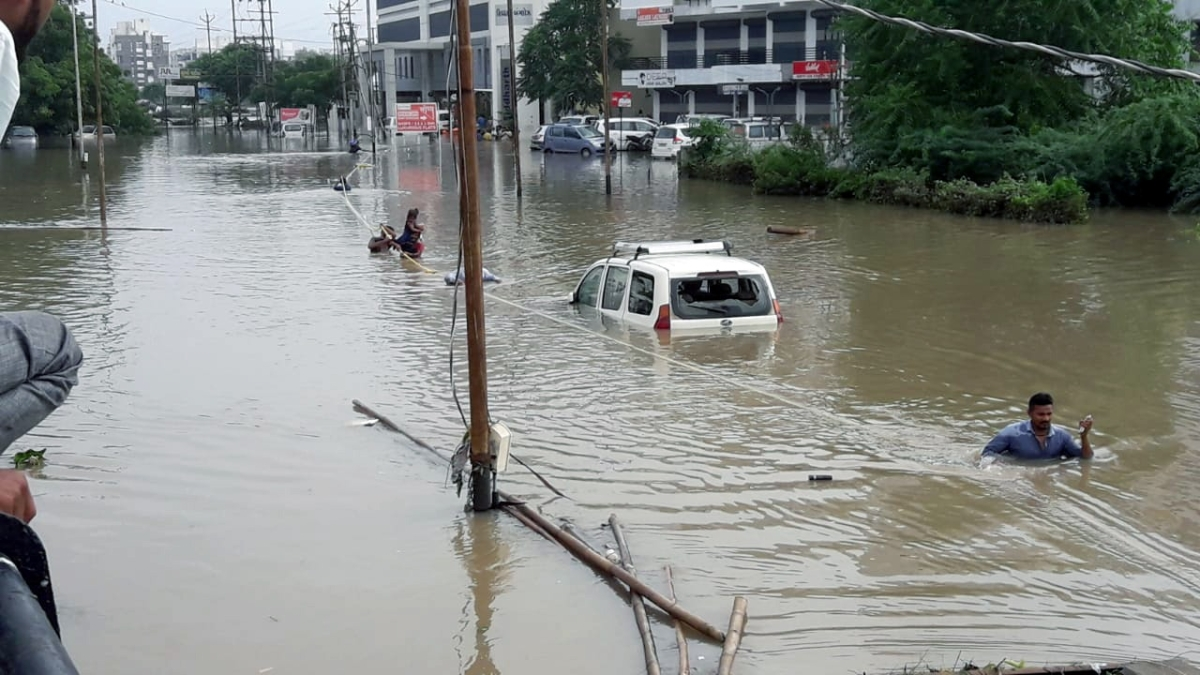 People cross a flooded road after the heavy rain at Ajitanagar in Vadodara, Gujarat
