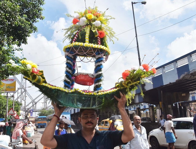 A devotee carrying puja materials from a market on the occasion of the Janmashtami Puja festival in Kolkata