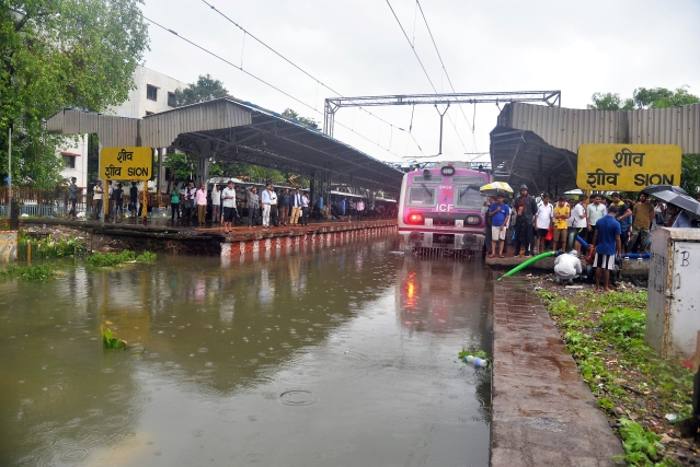 People wait for their train at flooded Sion Railway Station after heavy rainfall in Mumbai