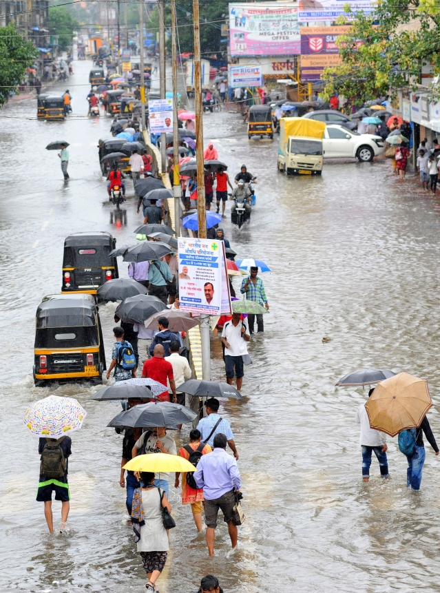 People walk on a flooded road after heavy rainfall at Nala Sopara in Mumbai