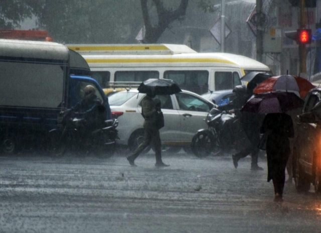 Pedestrians trying to cross an intersection during incessant rain at the Elphinstone area in Mumbai