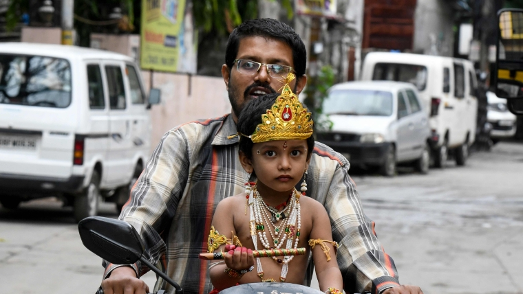 A man carries his son dressed as Hindu god Lord Krishna to school ahead of celebrations on the occasion of Janamashtami, the birthday of Lord Krishna, in Hyderabad on August 23, 2019