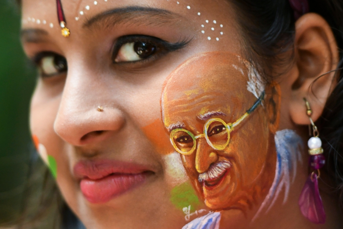 A girl poses for a picture with her face painted depicting a portrait of India's independence hero Mahatma Gandhi as the country celebrates its 73rd Independence Day, which marks the end of British colonial rule, in Bangalore