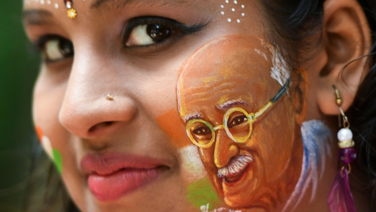 A girl poses for a picture with her face painted depicting a portrait of India's independence hero Mahatma Gandhi