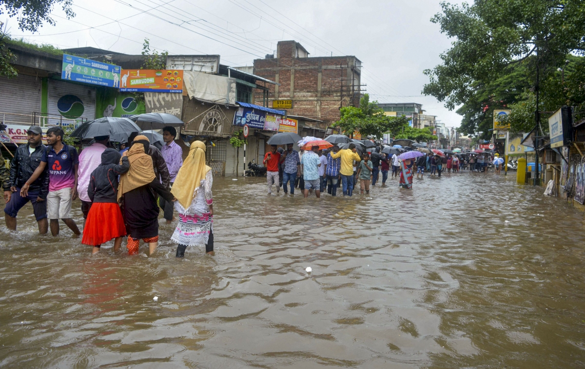 Pedestrians wade across a waterlogged street due to the overflow of Koyna river following monsoon rainfall, in Karad, Maharashtra