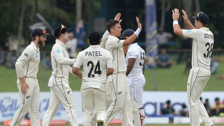New Zealand cricketer Trent Boult (C) celebrates with his teammates after he dismissed Sri Lankan cricketer Kusal Perera during the second day of the final cricket Test match at P. Sara Oval cricket stadium in Colombo