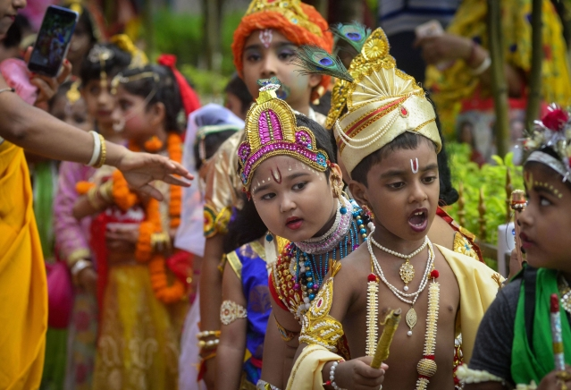 Students dressed up as Lord Krishna  take part in 'Janmashtami' festival celebrations at a school, in Agartala