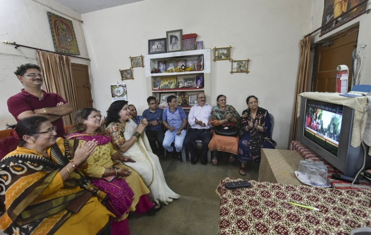 Members of a Kashmiri Pandit family clap as they watch the news on revokation of Article 370 in Jammu and Kashmir on a television, in Lucknow