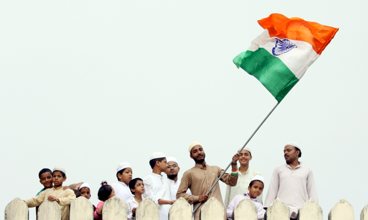 Students of Darul Uloom Nadwatul Ulama institution wave National flag on the occasion of Independence Day celebration at a college campus in Lucknow