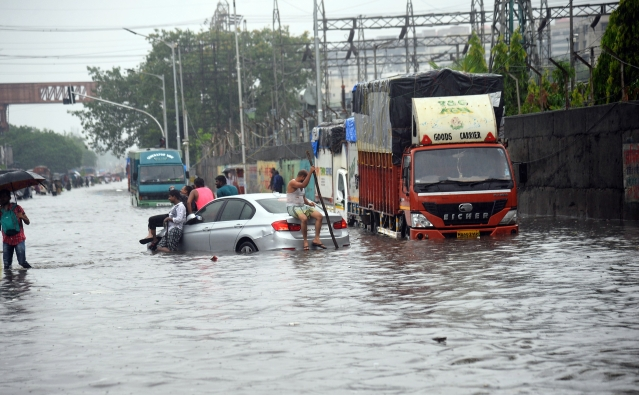 People sitting on a car on a flooded road after heavy rainfall at Sion in Mumbai