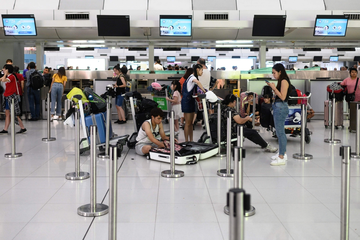 Tourists pack their luggages at Hong Kong's International Airport as all flights have been cancelled following a protest on August 13, 2019