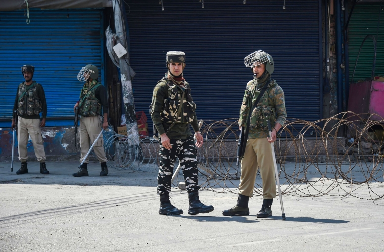 Security personnel stand guard during restrictions in Srinagar.