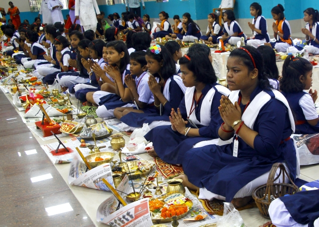 School students offer prayer during the mass worship on the occasion of 'Ganesh Chaturthi'  festival in Bhubaneswar