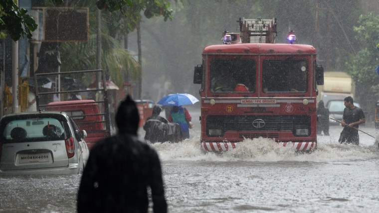 A fire engine drives through a flooded road during heavy rain showers in Mumbai on September 4, 2019.