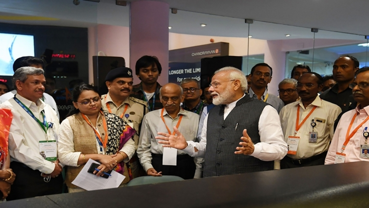 Prime Minister Narendra Modi (centre R) speaks with Indian Space Research Organisation (ISRO) scientists at the ISRO headquarters in Bangalore.