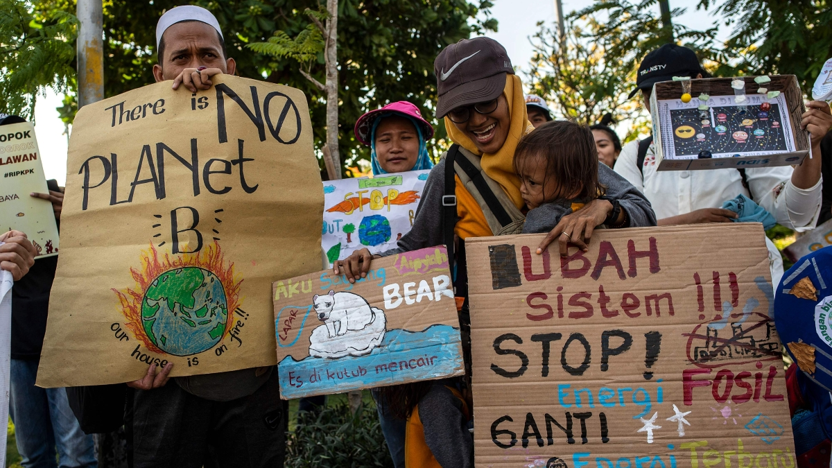 A group of Indonesians hold placards as they take part in a global climate change campaign in Surabaya on September 20, 2019.
