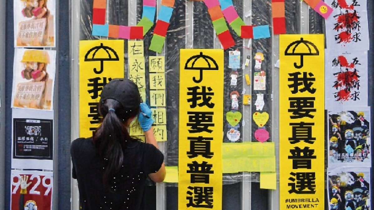 "A woman posts handbills and notes to help create a new ""Lennon Wall"" by the government offices in the Admiralty area in Hong Kong"