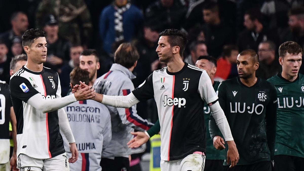 Juventus' Portuguese forward Cristiano Ronaldo (L) and Juventus' Uruguayan midfielder Rodrigo Bentancur tap hands at the end of the Italian Serie A football match Juventus vs Bologna on October 19, 2019