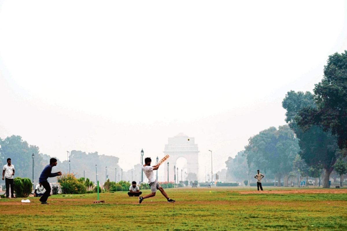 Youth play cricket in a park near India Gate under heavy smog in New Delhi on Tuesday. Several environmentalists have written to BCCI requesting to consider moving the T20 game out of Delhi.