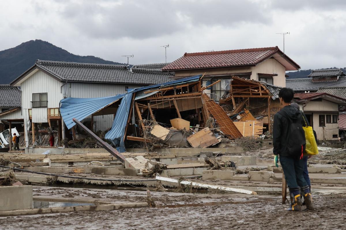 A man looks at flood-damaged homes in Nagano after Typhoon Hagibis hit Japan