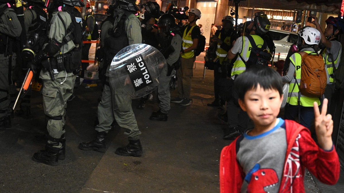 A boy poses for a photo in front of a group of riot police after a pro-democracy rally in Yuen Long district of Hong Kong on November 21, 2019.