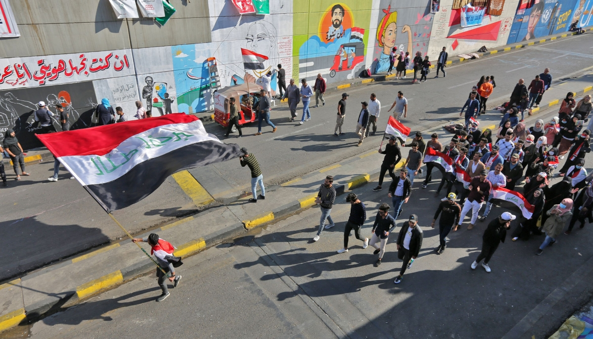Iraqi youths waving national flags march through Tahrir Square in the Iraqi capital Baghdad as anti-government protests continued across the country.