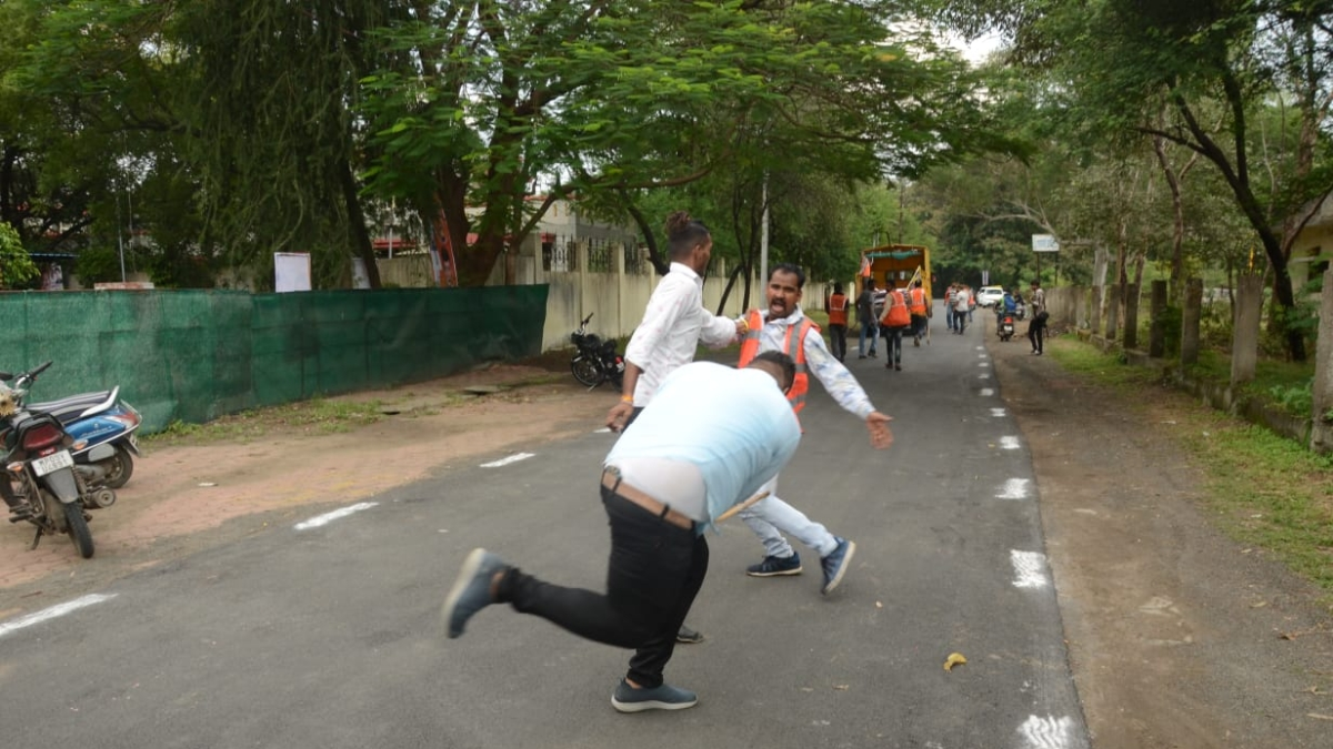 Congress activists beating IMC employees with stick.