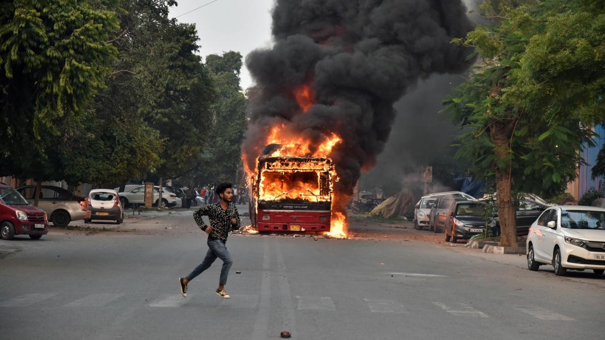 Delhi Transport Corporation (DTC) buses set ablaze by protesters over the Citizenship Amendment Act near Jamia Nagar in New Delhi on Sunday.