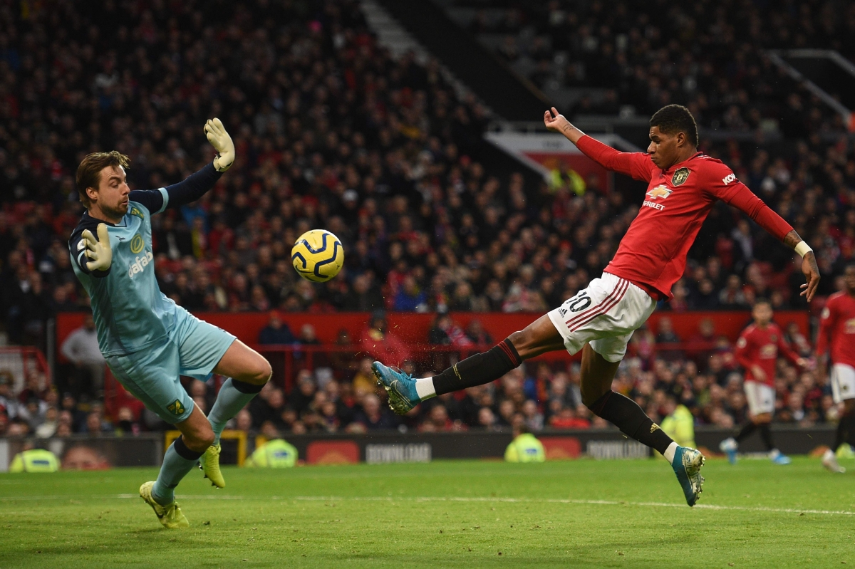 Manchester United's English striker Marcus Rashford (R) puts the ball past Norwich City's Dutch goalkeeper Tim Krul (L) to score the opening goal during the English Premier League football match between Manchester United and Norwich City at Old Trafford in Manchester, north west England, on January 11, 2020.