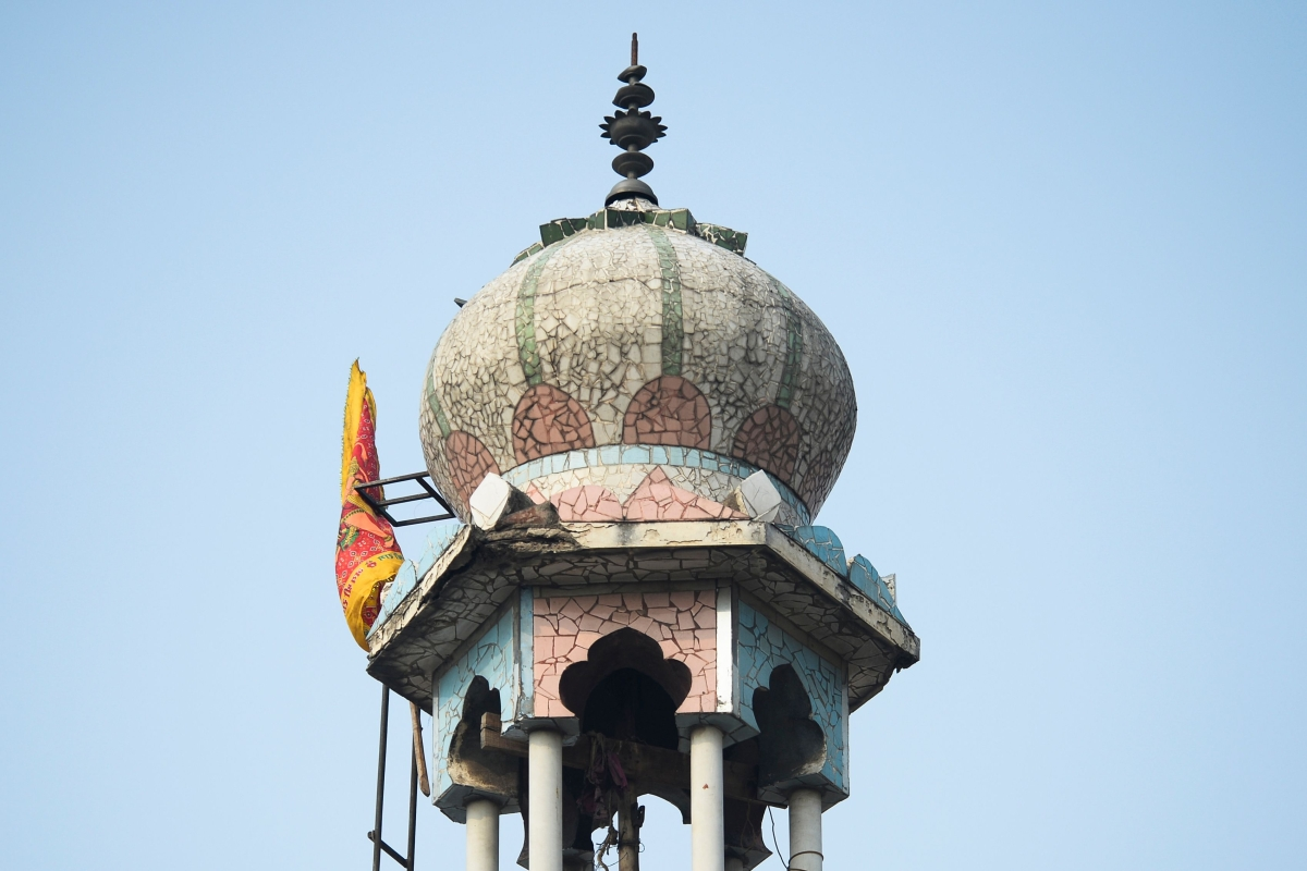 A Hindu religious flag is seen on a minaret of a burnt-out mosque following clashes between people supporting and opposing a contentious amendment to India's citizenship law, in New Delhi on February 26, 2020.