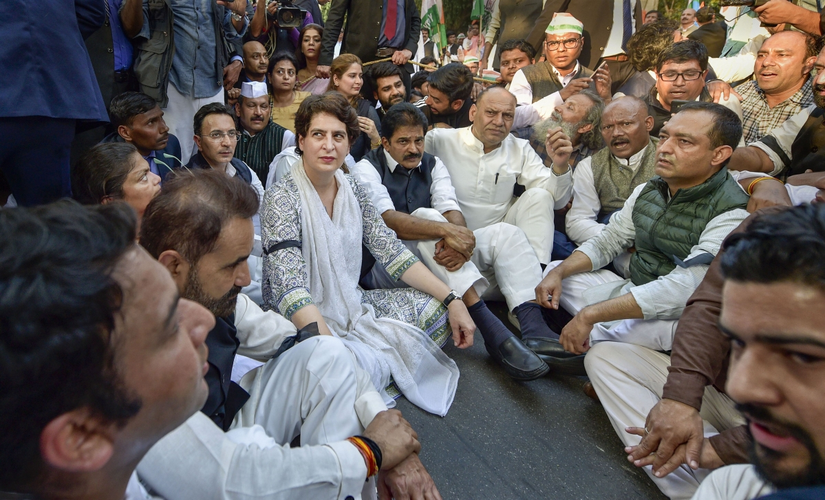 AICC General Secretary Priyanka Gandhi Vadra along with party workers sits on a street after being stopped by police officials during a peace march from AICC Headquarters to 30 January Marg against the communal violence in North-East Delhi area, in New Delhi on Wednesday.