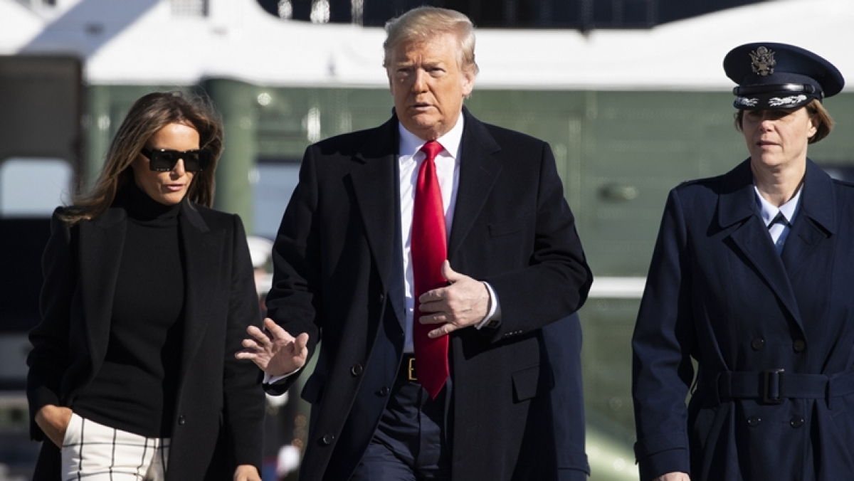 President Donald Trump, with First Lady Melania Trump, wave as they walk across the tarmac to board Air Force One during their departure on Sunday, Feb. 23, 2020
