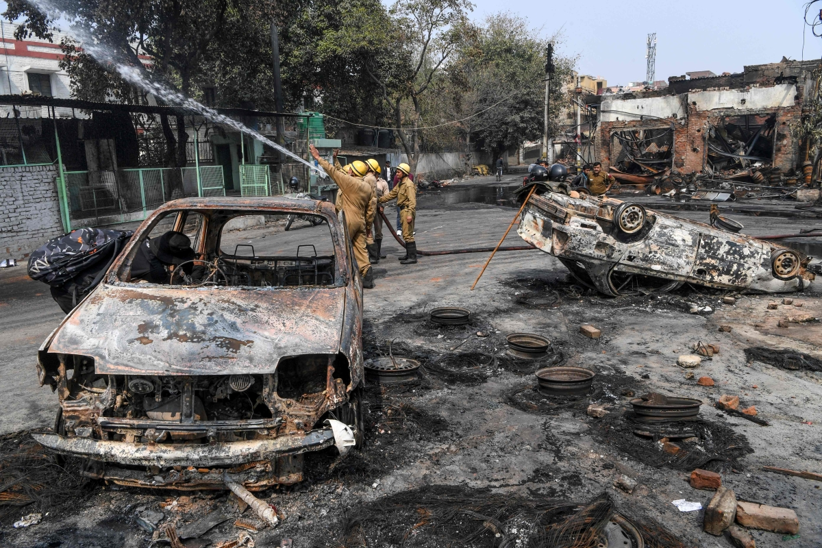 Firefighters hold a water pipe to douse burnt-out tyre market premises following clashes between people supporting and opposing a contentious amendment to India's citizenship law, in New Delhi on February 26, 2020.