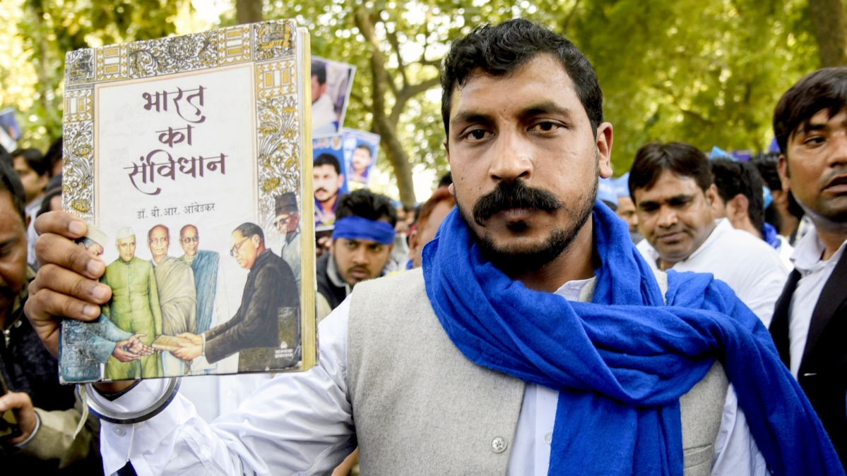 Bhim Army chief Chandrashekhar Azad shows the book of Indian Constitution during a protest march from Mandi House to Jantar Mantar, in New Delhi on Sunday.